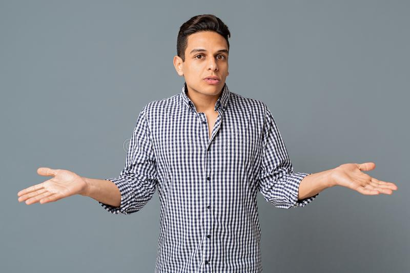Portrait On Confused Young Man Shrugging Shoulders On Gray Background. I Don`t Know. Unsure Arab Man Shrugging Shoulders On Gray Studio Background royalty free stock photography