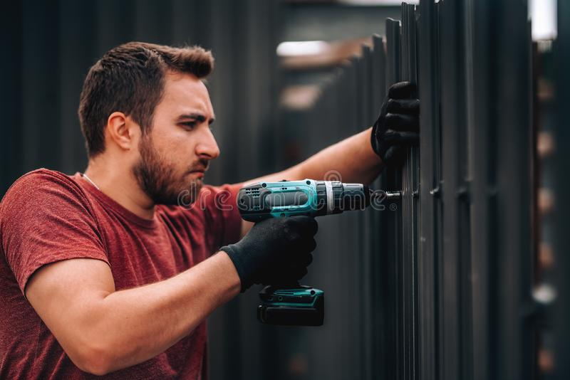 construction worker installing metal elements using cordless screwdriver royalty free stock image