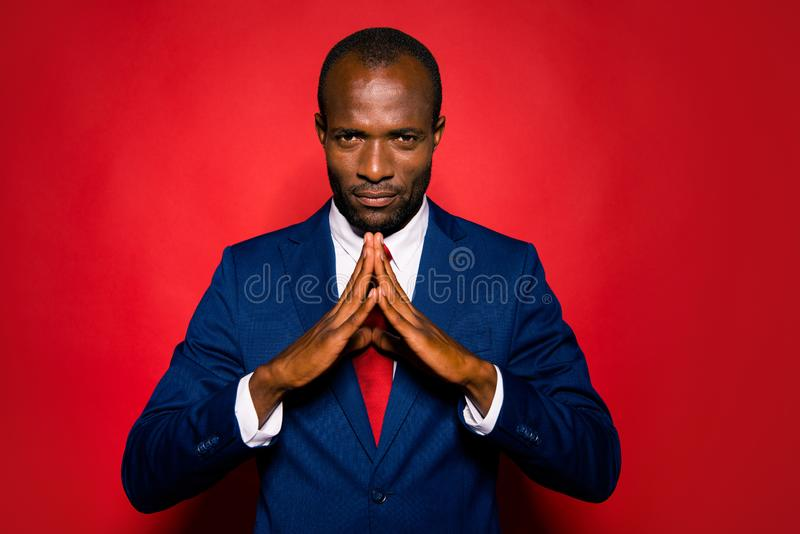 Portrait of content focused conentrated handsome authoritative m. Ulatto rich wealthy man executive manager wearing blue suit folded hands isolated over red stock image