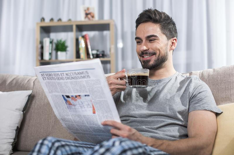 Glad man relaxing with newspaper royalty free stock photo