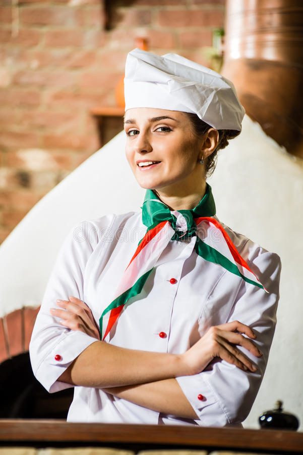 Portrait of a cook. Is on the traditional kitchen, crossed her arms stock image