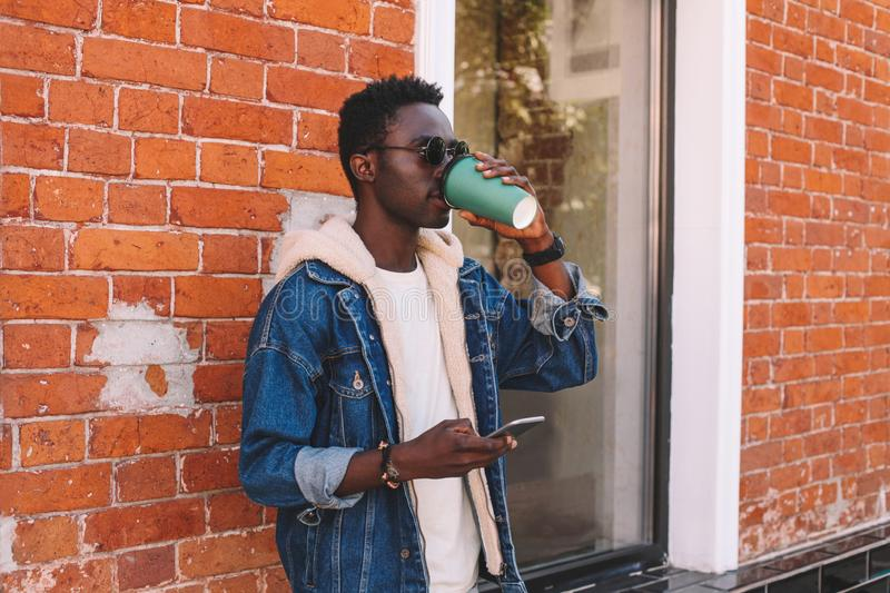 Portrait cool african man drinking coffee holding phone in hand standing on city street over brick wall. Background stock images
