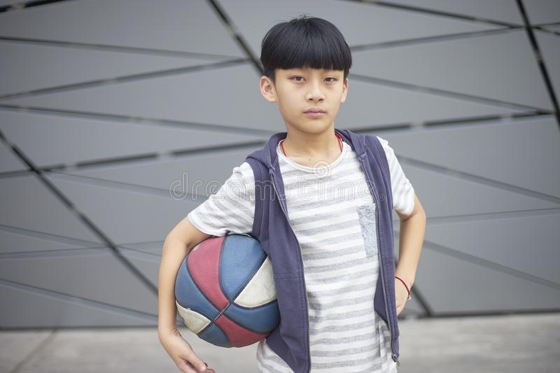 Portrait of cool Asian kid holding basketball outdoors stock photo