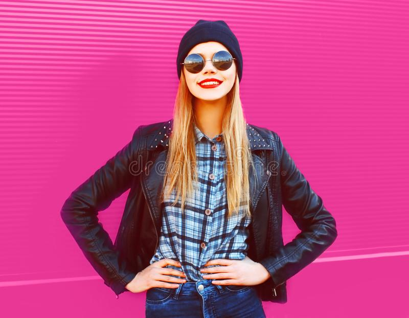 Portrait cool blonde smiling girl in rock black style jacket, hat posing on city street over colorful pink wall royalty free stock photos