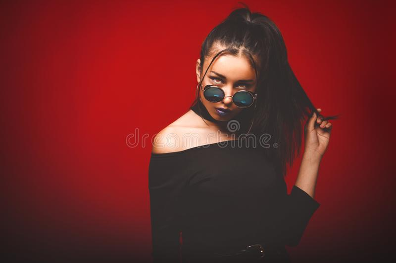 Portrait of cool crazy brunette fashionable girl in sunglasses,. Casual hairdo on red background. Woman like bitch with pretty makeup big lips stock photos
