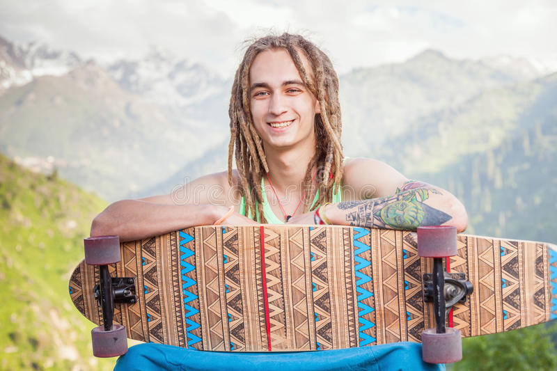 Portrait of cool, funny handsome man with skateboard at mountain stock photos