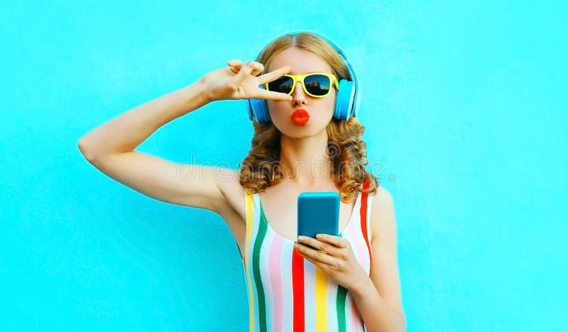 Portrait cool girl blowing red lips sending sweet air kiss holding phone listening to music in wireless headphones on colorful royalty free stock photography