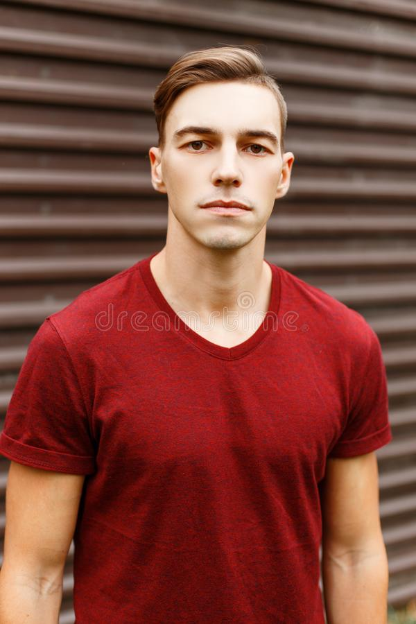 Portrait of a cool handsome young man in a fashionable red t-shirt with a stylish hairstyle near a vintage metal building. royalty free stock photography