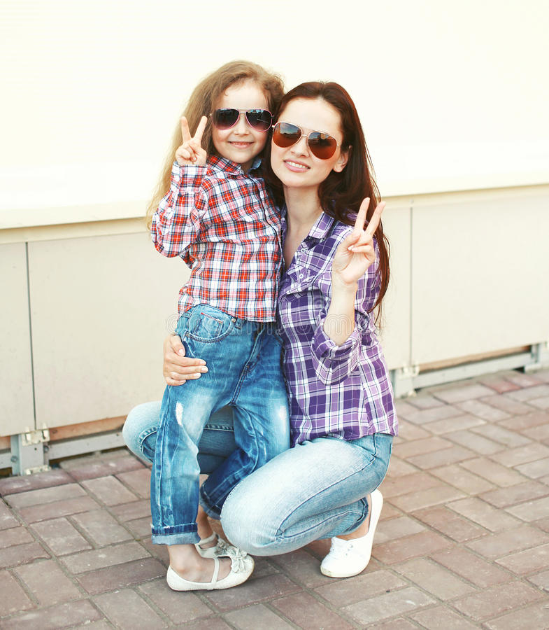 Portrait cool mother and child wearing a checkered shirts and sunglasses stock image