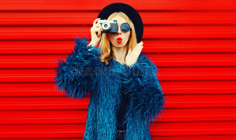 Portrait cool surprised woman with retro camera taking picture wearing blue faux fur coat, round hat and sunglasses royalty free stock photography