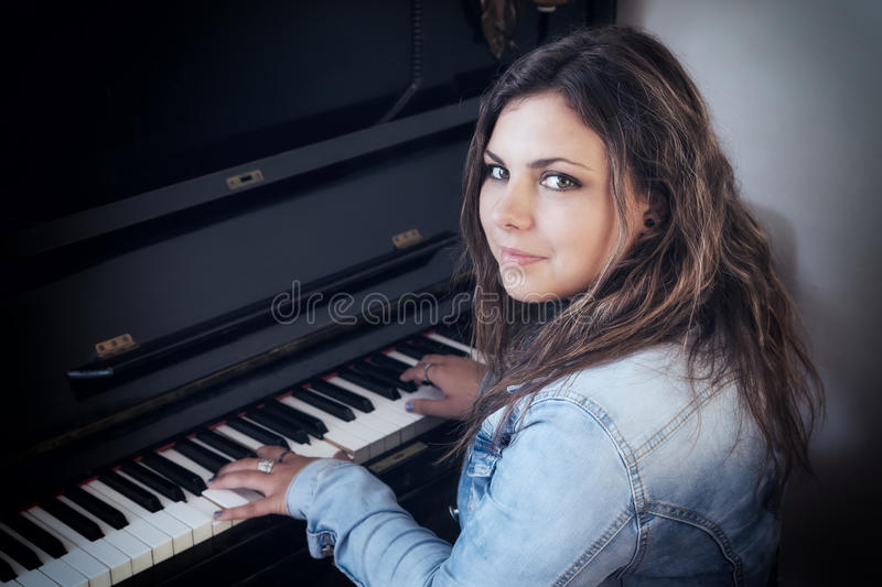 Portrait of cool teenage girl playing the piano royalty free stock images
