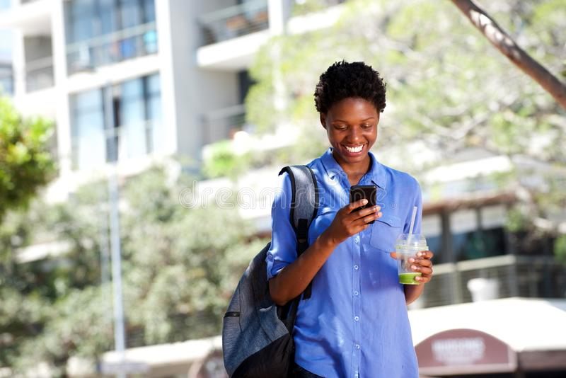 Cool young african woman walking outdoors in city using mobile phone. Portrait of cool young african woman walking outdoors in city using mobile phone royalty free stock photo