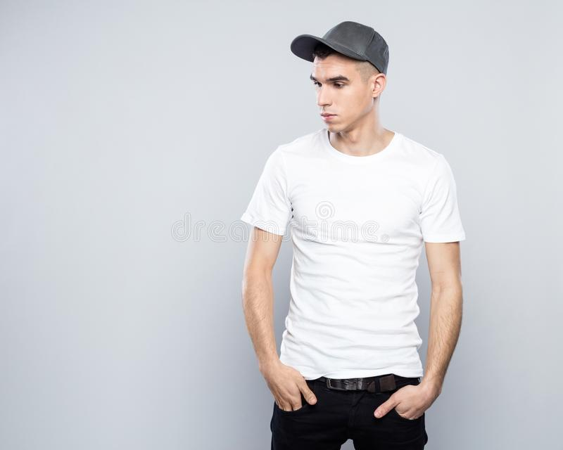 Portrait of cool young man in baseball cap and white t-shirt. Studio shot of confident young man wearing white t-shirt and baseball cap, standing against grey royalty free stock image