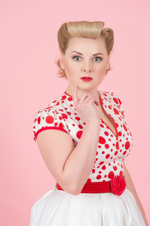 Portrait with copyspace of pretty cute pin-up styled woman holding fingers on chin and looking at camera. blonde woman stock photo
