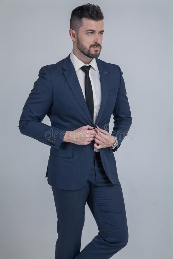 Portrait with copy space of stunning, fashionable, cool, virile, rich man with stubble in blue suit fasten button on jacket with stock photos