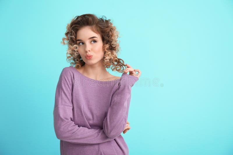 Portrait of coquettish young woman in casual clothes on color background stock photo