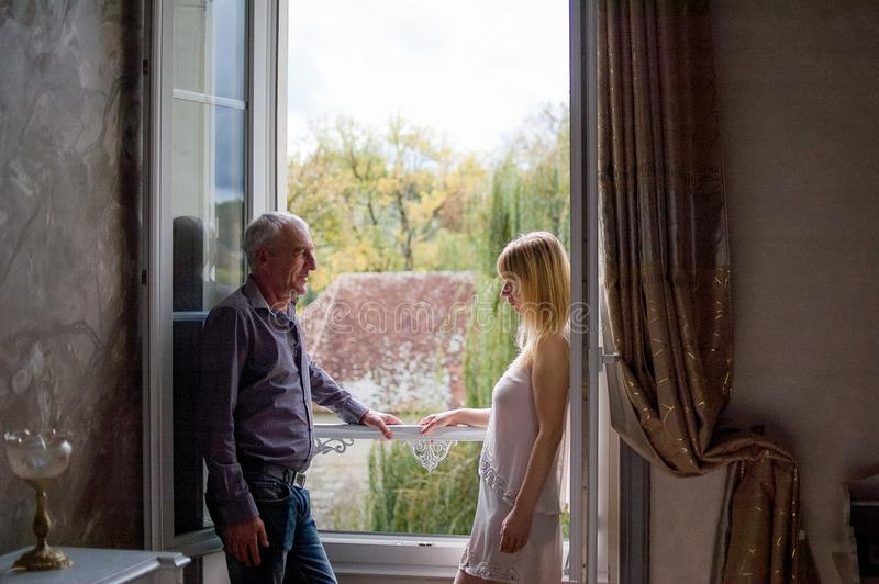 Portrait of Couple with Age Difference Standing near Opened Window inside the House During Summer Sunny Day. Portrait of Couple with Age Difference Standing stock photo