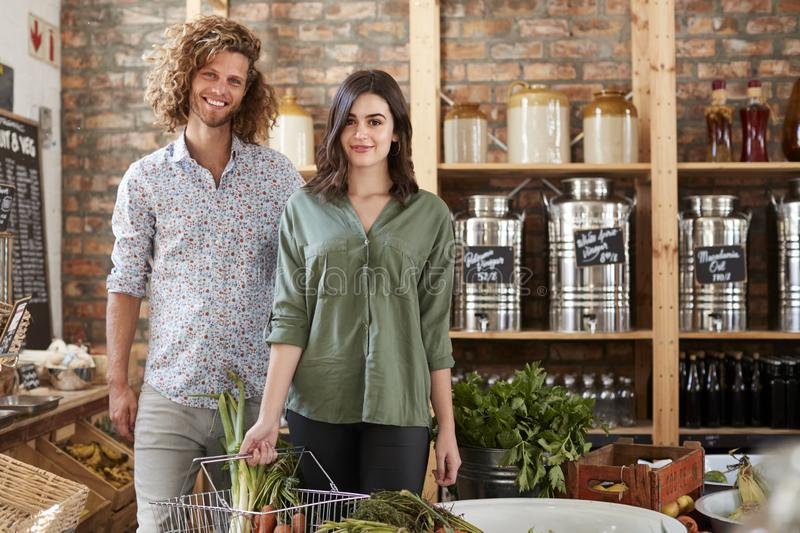 Portrait Of Couple Buying Fresh Fruit And Vegetables In Sustainable Plastic Free Grocery Store stock images