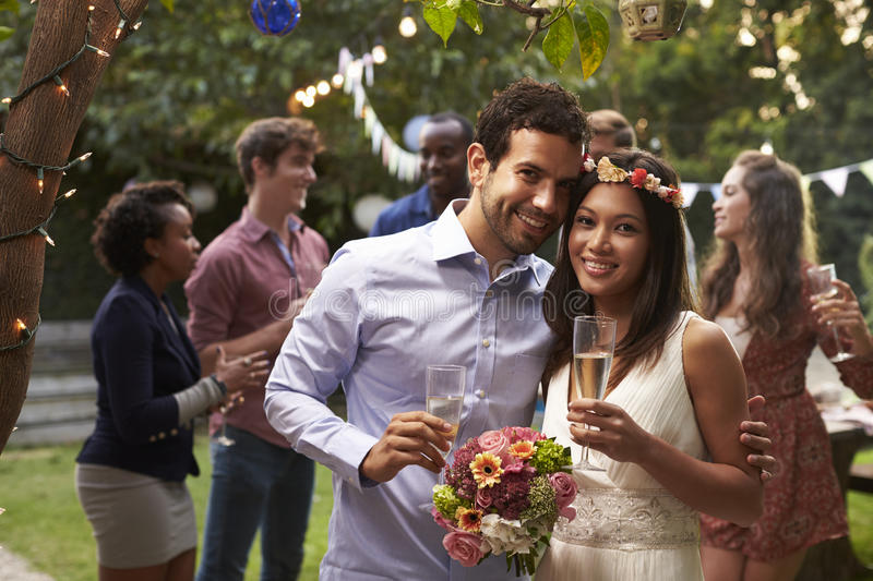 Portrait Of Couple Celebrating Wedding With Backyard Party stock photography