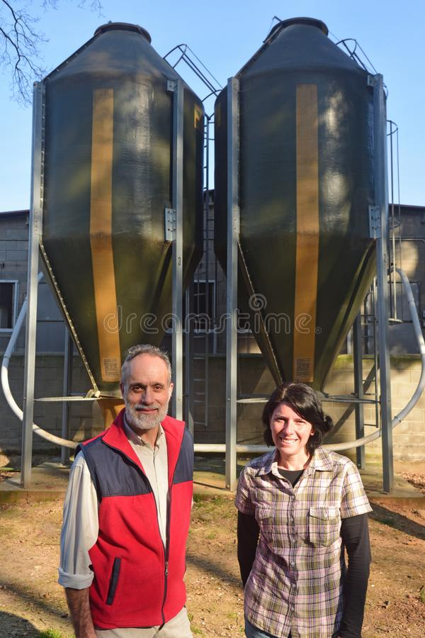 Portrait of a couple farmers on the outside of a grange with grain storege.  stock images