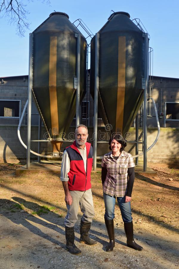 Portrait of a couple farmers on the outside of a grange with grain storege.  royalty free stock photos