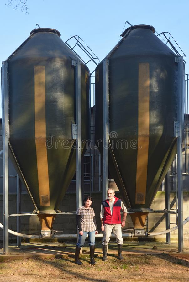 Portrait of a couple farmers on the outside of a grange with grain storege.  royalty free stock photo