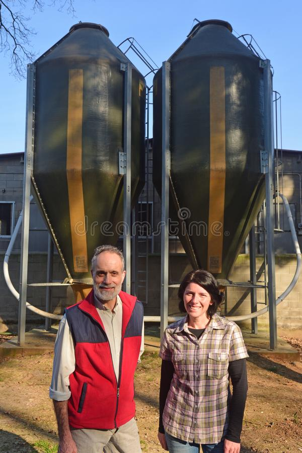 Portrait of a couple farmers on the outside of a grange with grain storege.  stock photos
