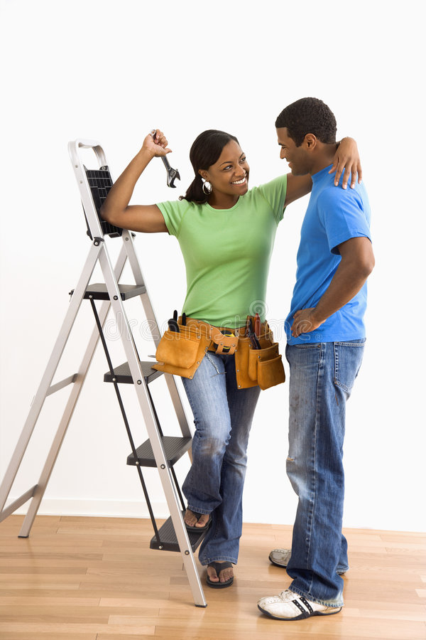 Portrait of couple with ladder. Portrait of smiling African American male and female couple with home repair tools and ladder stock photo