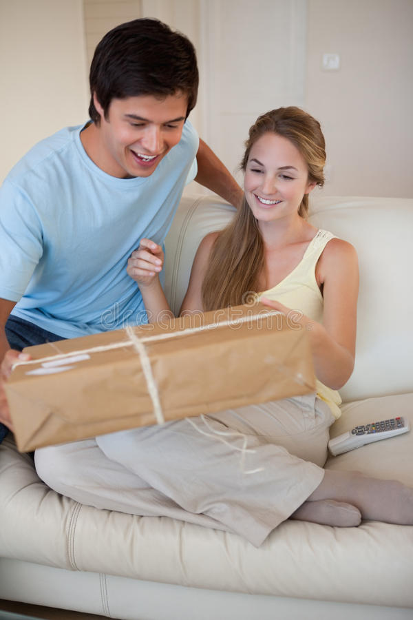 Portrait of a couple looking at a package. In their living room royalty free stock photos