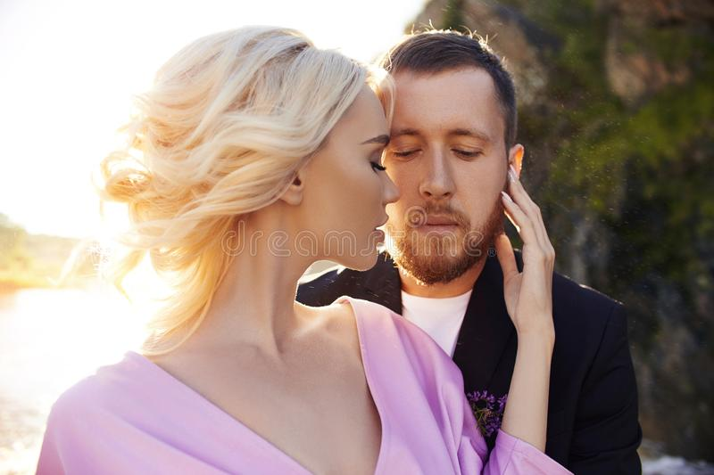 Portrait of a couple in love close-up on a beautiful Sunny day at sunset. Love emotions and hugs in the sun. Blonde woman and man stock photo