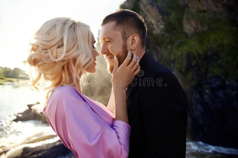 Portrait of a couple in love close-up on a beautiful Sunny day at sunset. Love emotions and hugs in the sun. Blonde woman and man. Portrait of a couple in love stock image
