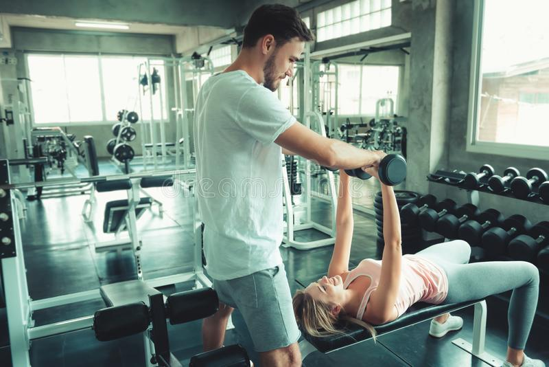 Portrait of Sporty Couple Love Exercised in Fitness Training With Dumbbell Equipment., Young Couple Caucasian are Working Out and. Training Together in Gym Club stock photography