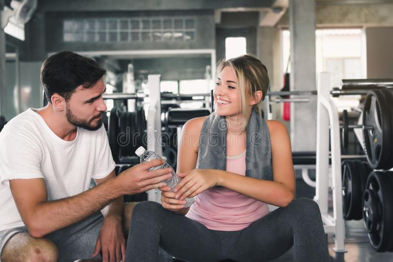Portrait of Couple Love Sporty in Fitness Club, Handsome Man Giving a Bottle of Drinking Water to His Girlfriend After Working Out royalty free stock images