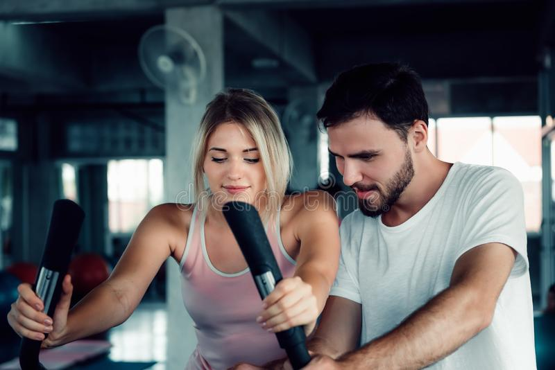 Portrait of Couple Love is Workout in Fitness Gym Together. Attractive Woman is Working Out Bike Cycling with Her Exercise Trainer stock photos