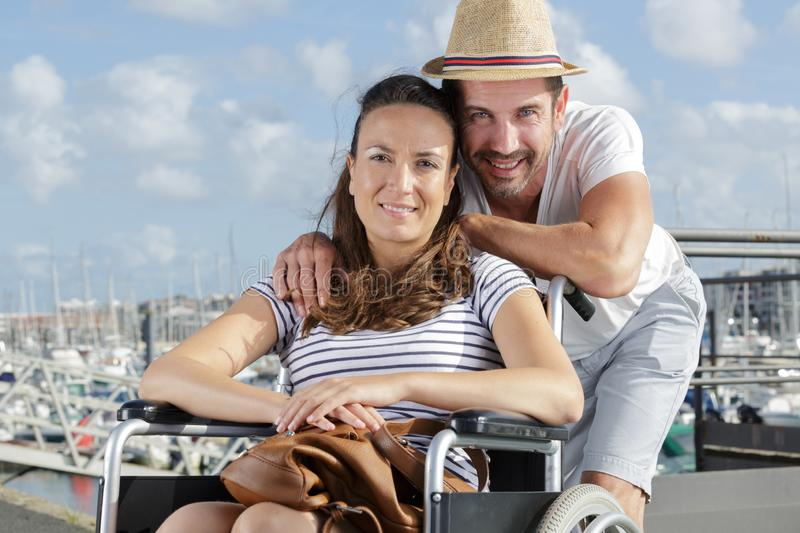Portrait couple at marina woman in wheelchair royalty free stock images