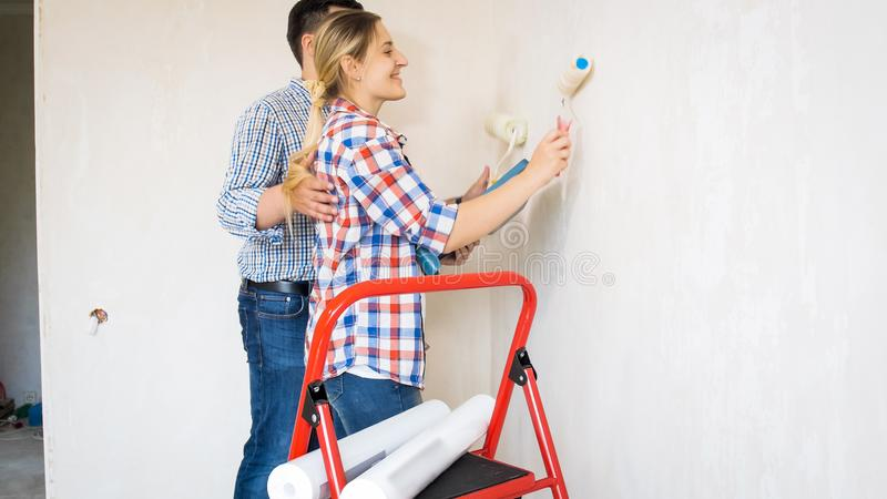 Portrait of young couple painting walls in new house with white paint. Portrait of couple painting walls in new house with white paint stock photos