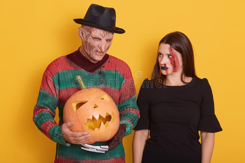 Portrait of couple posing with pumpkin for Halloween against yellow background, woman wearing dress, having bloody wound on her stock photo
