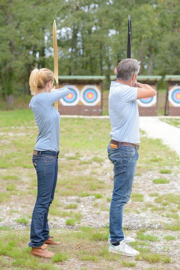 Portrait couple practicing archery stock images