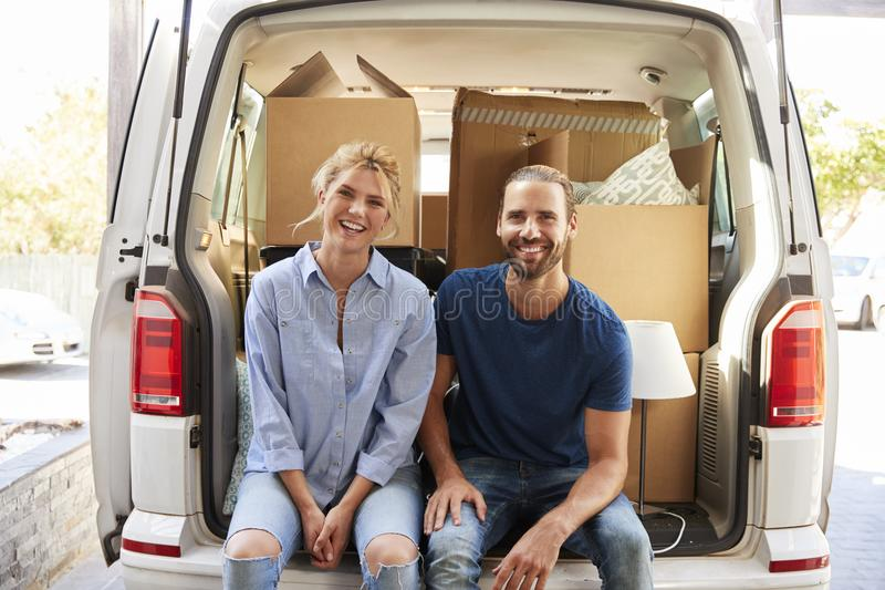 Portrait Of Couple Sitting In Back Of Removal Truck On Moving Da. Y stock photography