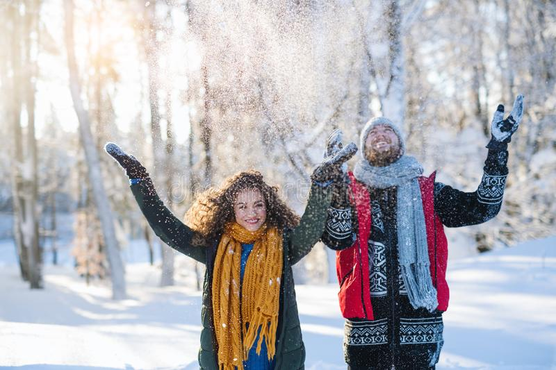 Portrait of couple standing outdoors in snow in winter forest, throwing snow. royalty free stock images