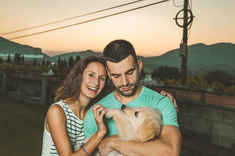 Portrait of a couple with their adorable puppy dog stock images