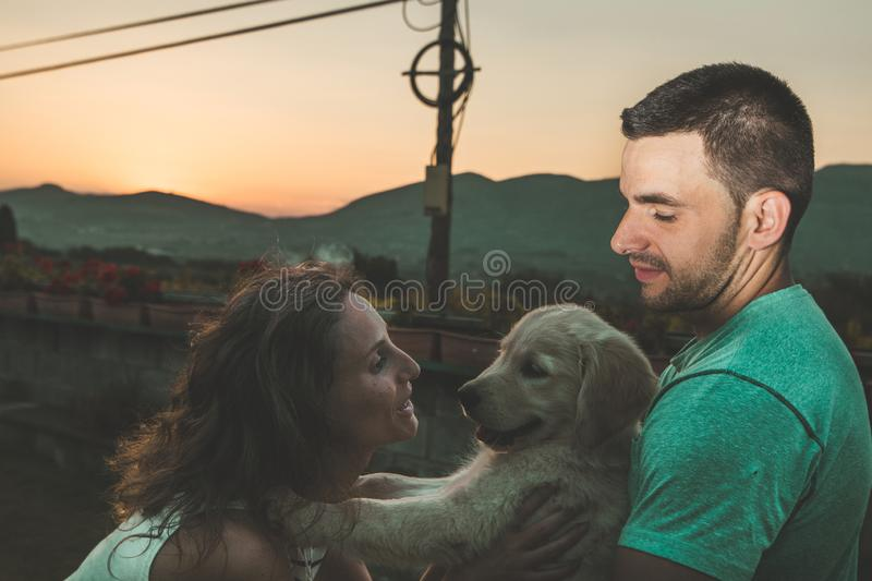 Portrait of a couple with their adorable puppy dog royalty free stock photo