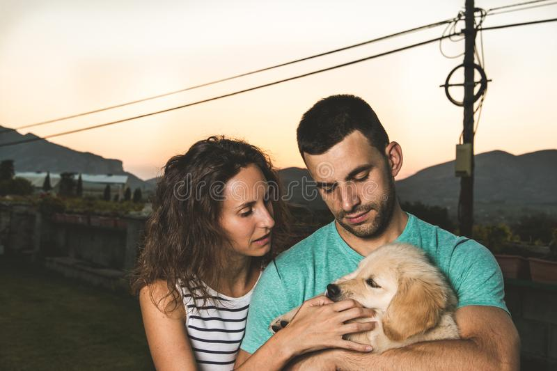 Portrait of a couple with their adorable puppy dog stock photo
