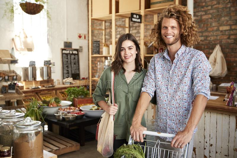 Portrait Of Couple With Trolley Buying Fresh Fruit And Vegetables In Plastic Free Grocery Store stock photo