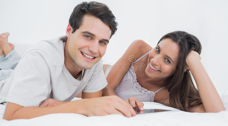 Download Portrait Of A Couple Using A Tablet Lying In Bed Stock Image - Image of bedroom, caucasian: 32509709