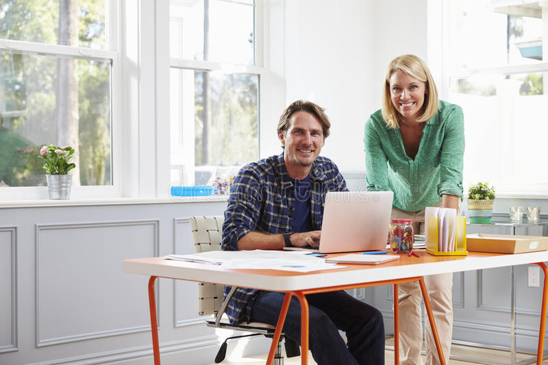 Portrait Of Couple Working Together At Desk In Home Office royalty free stock photo