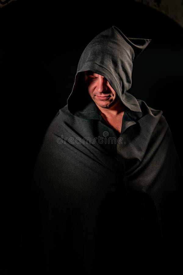 Portrait of a courageous warrior wanderer in a black cloak. Historical fantasy. Halloween. Portrait of a courageous warrior wanderer in a black cloak stock photos