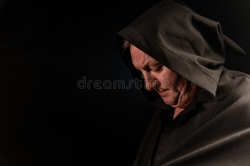 Portrait of a courageous warrior wanderer in a black cloak. Historical fantasy. Halloween. Portrait of a courageous warrior wanderer in a black cloak royalty free stock photos