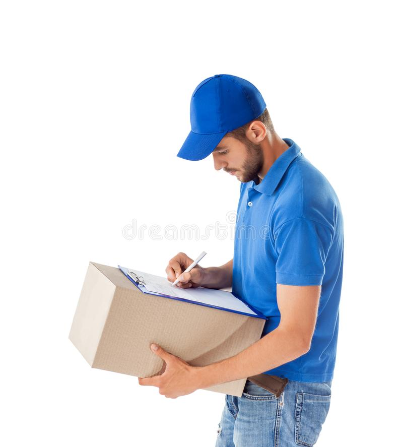 Portrait of courier fills paper on delivery box isolated on whit. E background royalty free stock image
