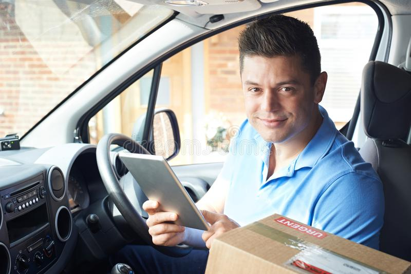 Portrait Of Courier In Van With Digital Tablet Delivering Package To House royalty free stock image